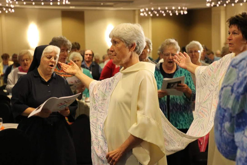 """Altar cloth with names written """"in honor of all those, living or deceased, who have been an inspiration and model of unstoppable charity."""""""